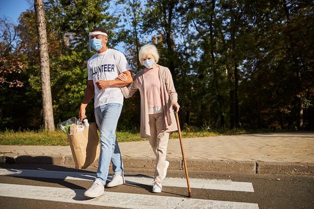 Signora anziana appoggiata a un bastone da passeggio e tenendo un volontario sotto il gomito mentre attraversava la strada con lui