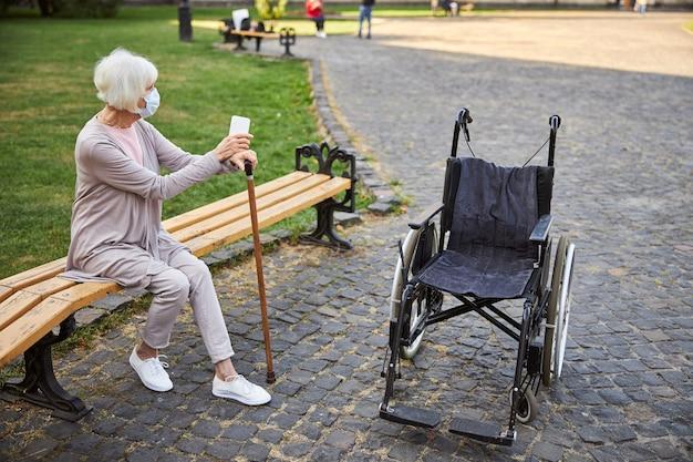 Signora anziana in maschera medica seduta su una panchina con le mani su un bastone da passeggio e guardando lontano. sedia a rotelle vuota davanti a lei