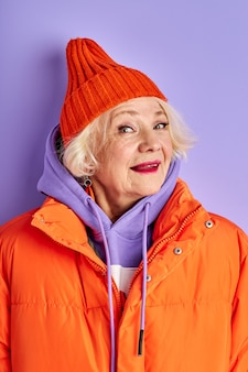 Signora anziana in posa isolato in studio su spazio viola, signora matura guarda la fotocamera e sorride, indossa un cappotto caldo arancione