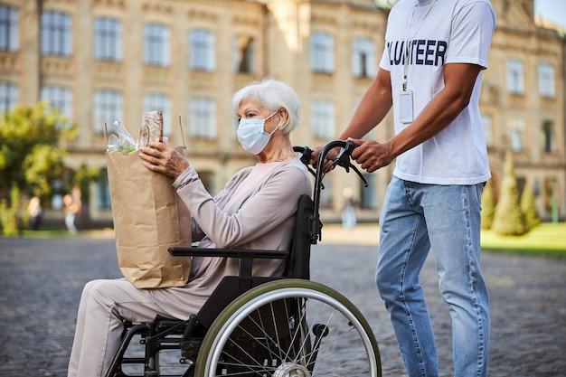 Signora anziana seduta su una sedia a rotelle con una borsa della spesa piena di cibo. volontario non riconosciuto che spinge le maniglie