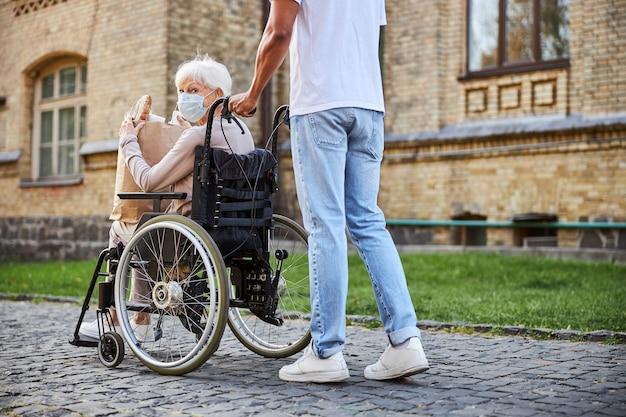 Signora anziana con disabilità che tiene in mano un sacchetto di carta con gli acquisti e torna indietro mentre il giovane spinge la sedia a rotelle