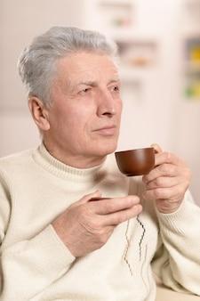 Uomo anziano che beve una tazza di caffè, primo piano