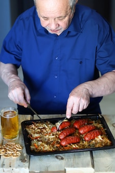 Uomo anziano che mangia salsicce e beve birra