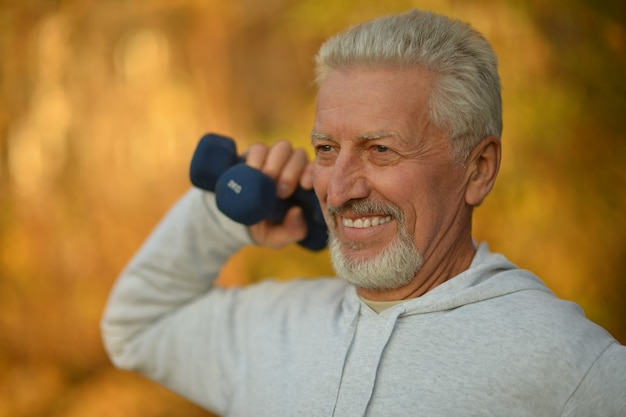 Uomo anziano che si esercita con i manubri nel parco autunnale