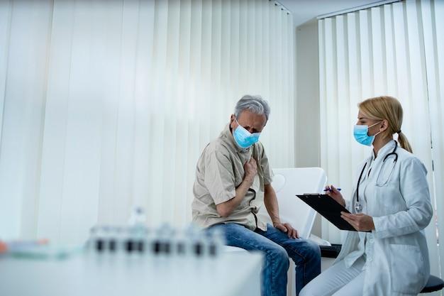 Un uomo anziano che non si sente bene mentre il medico annota i sintomi durante la pandemia covid19
