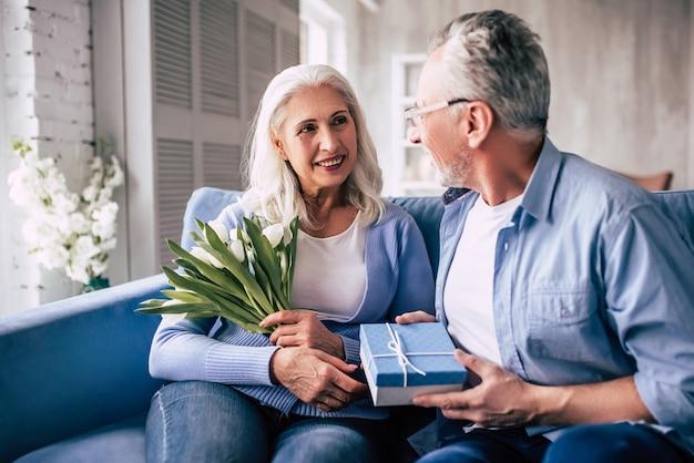 L'anziano che fa un regalo a una donna con dei fiori