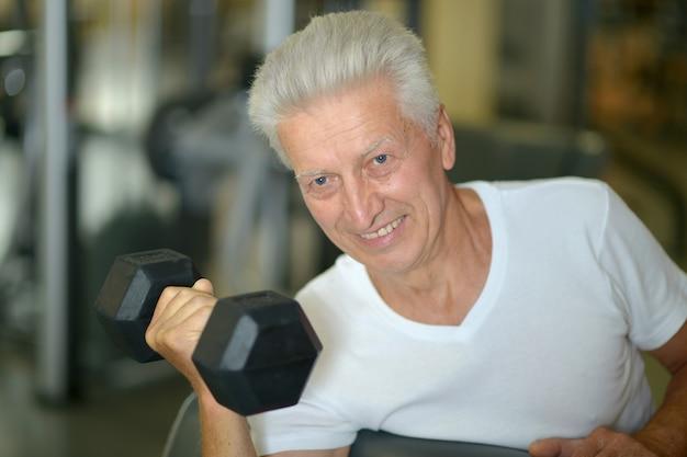 Uomo anziano in una palestra. allenarsi con i manubri