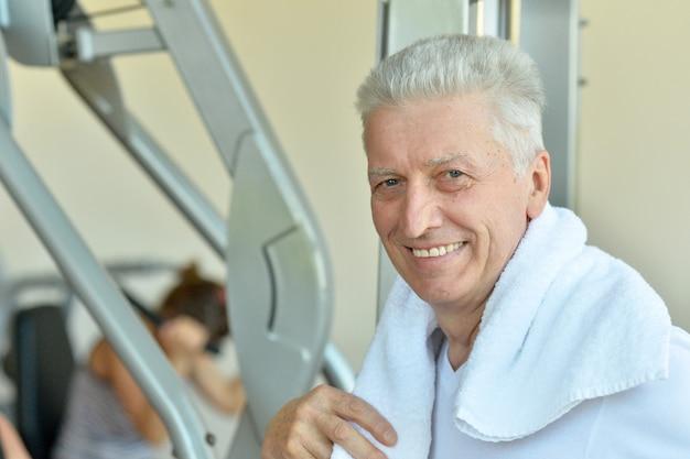 Uomo anziano in una palestra. riposo dopo l'esercizio