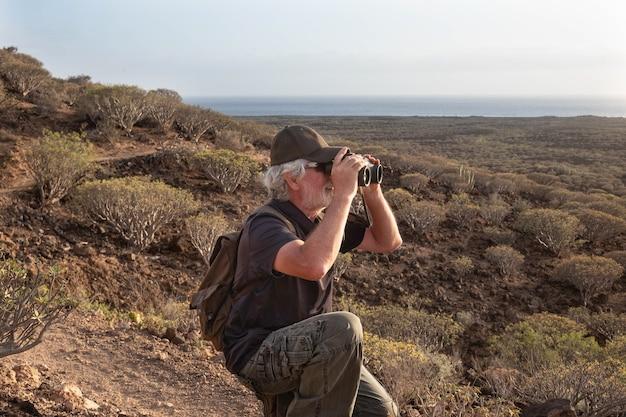 Uomo anziano che fa un'escursione in montagna e si ferma a guardare il paesaggio con un binocolo. buona escursione all'aperto. giovani anziani in uno stile di vita sano