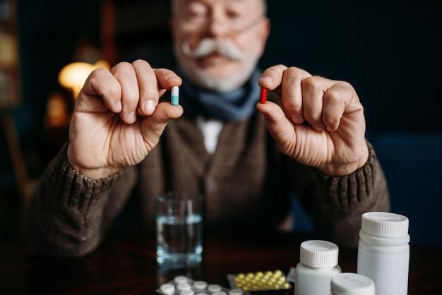 L'uomo anziano tiene le pillole nelle sue mani, ufficio a casa sul nero