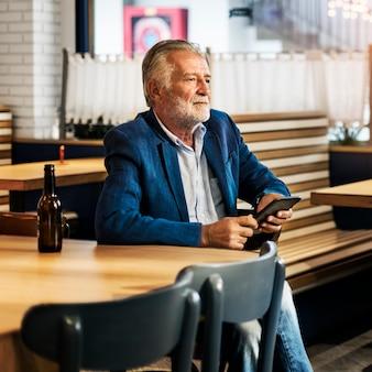 L'uomo anziano è seduto in un pub