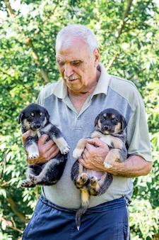 Un uomo anziano tiene in mano due cuccioli