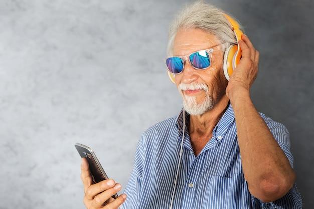 L'uomo anziano ascolta musica con le cuffie