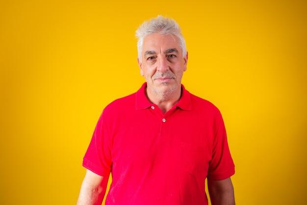 Uomo anziano che guarda l'obbiettivo su sfondo giallo con spazio per il testo.