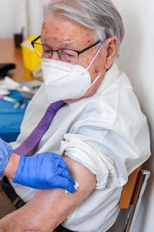 Un uomo anziano con la maschera guarda l'infermiera in tuta protettiva e la maschera covid gli dà il vaccino contro il coronavirus