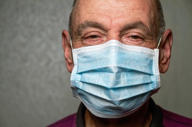 Un uomo anziano con una mascherina medica. gruppo a rischio. concetto di covid-19. malattia di coronavirus. avvicinamento
