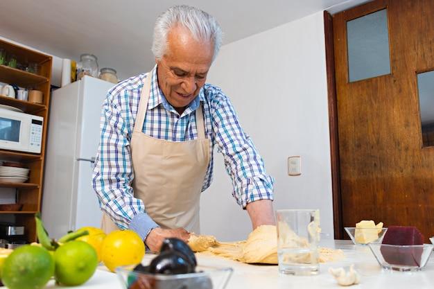 Un uomo anziano che mescola doug con le mani su un tavolo, in cucina, con indosso un grembiule