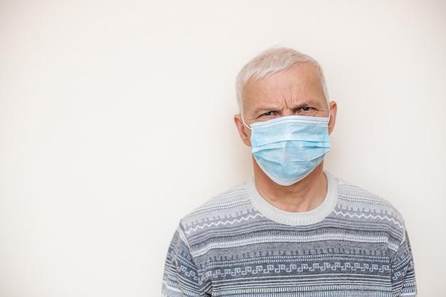 Uomo anziano nell'isolato medico protettivo della maschera nel bianco. coronavirus consigli per anziani. uomini anziani di sicurezza.