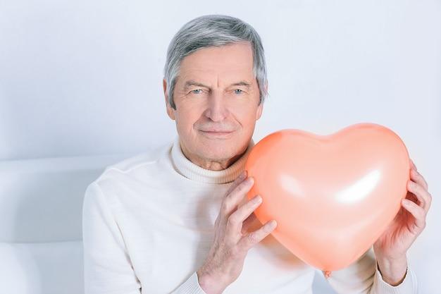 Uomo anziano che mostra un grande cuore.isolato su bianco