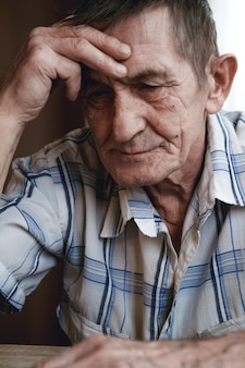 L'uomo anziano si siede tenendo la testa, soffre di perdita di memoria