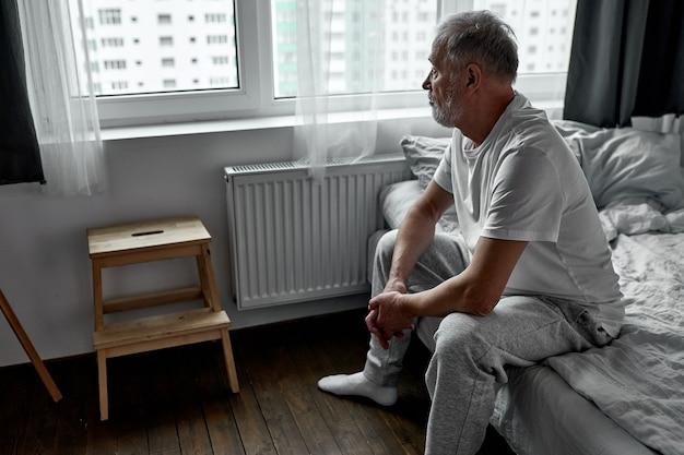 Uomo anziano seduto da solo a casa, allontanamento sociale e auto isolamento in blocco da quarantena per coronavirus