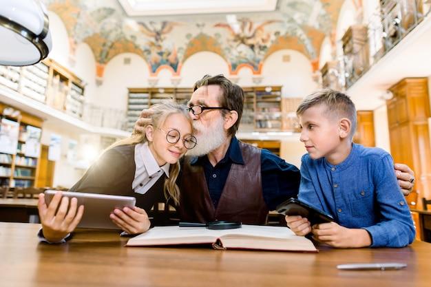 Insegnante uomo anziano e suoi studenti adolescenti, ragazzo e ragazza, seduto al tavolo in biblioteca