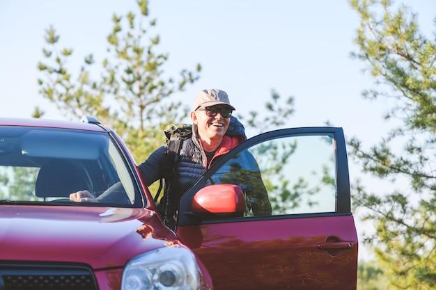 Uomo anziano in abiti turistici e occhiali da sole nella foresta