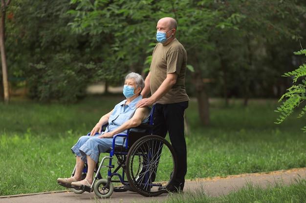 Uomo anziano che cammina con donna anziana disabile seduta in sedia a rotelle all'aperto