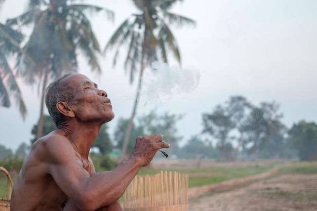 L'uomo anziano era seduto a fumare