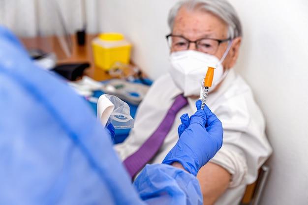 Un uomo anziano guarda l'infermiera in tuta protettiva e guanti sanitari mentre prepara il suo vaccino contro il coronavirus