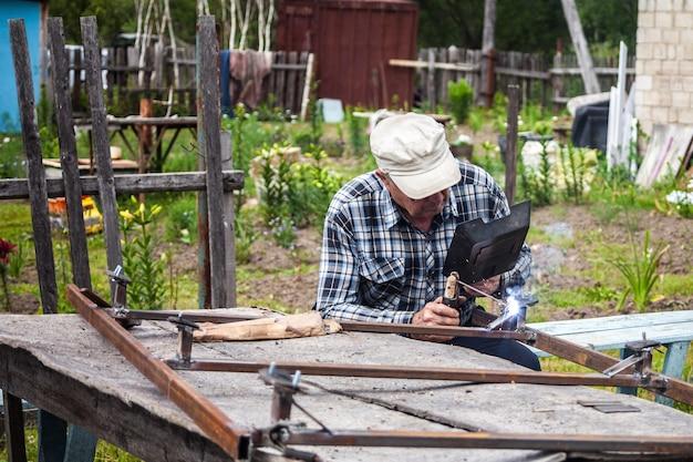 Uomo anziano che salda la costruzione in metallo al giardino