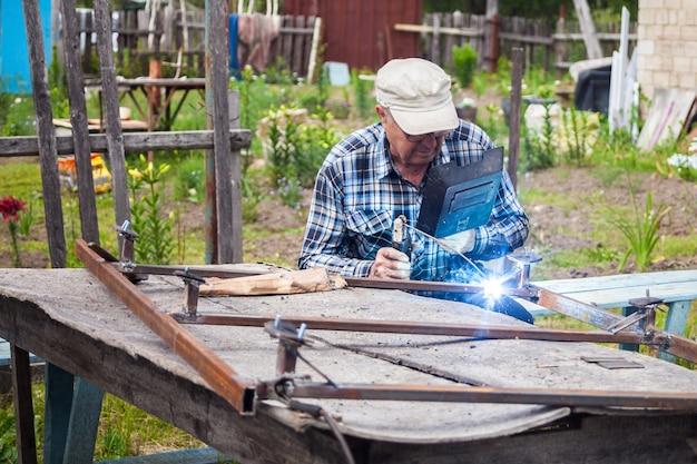 Uomo anziano che salda la struttura metallica al giardino