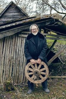 Un uomo anziano con la barba si trova nel villaggio vicino a un capannone di legno con un cappotto di pelle di pecora e occhiali