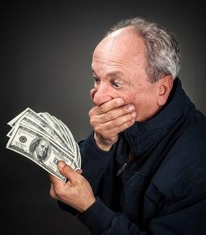 Uomo anziano con un fan di dollari