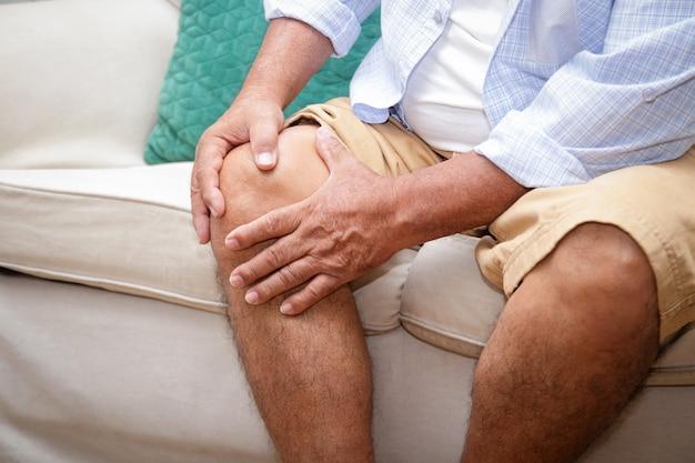 Un uomo anziano con un dolore al ginocchio seduto su un divano di casa