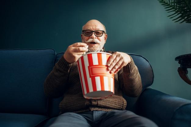 Uomo anziano con popcorn guardando la tv sul divano in ufficio a casa. barbuto anziano maturo pone in soggiorno, uomo d'affari di vecchiaia