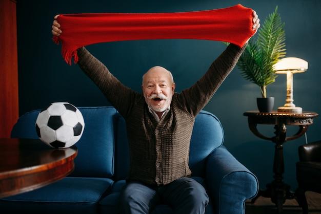Uomo anziano con sciarpa rossa e palla a guardare la tv, appassionato di calcio. barbuto anziano maturo pone in soggiorno, persone di vecchiaia svaghi