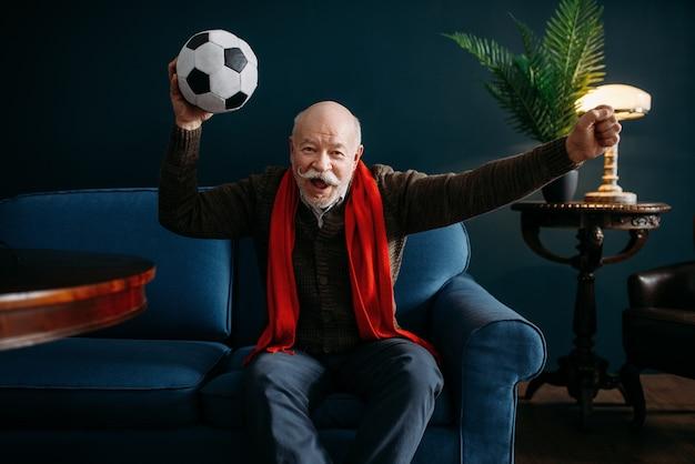 Uomo anziano con sciarpa rossa e palla che guarda la tv, tifoso di calcio