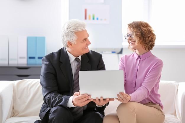 Uomo anziano e giovane donna seduta sul divano in ufficio