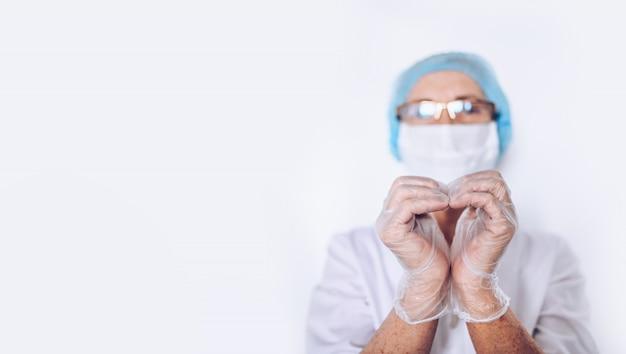 Il medico o l'infermiere maturo anziano della donna che mostra il cuore firma dentro un cappotto medico bianco, i guanti, maschera di protezione che indossa l'attrezzatura protettiva personale isolata. concetto di sanità e medicina. pandemia di covid-19