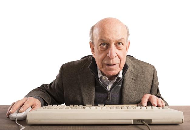 Il nerd anziano lavora con la sua tastiera vintage
