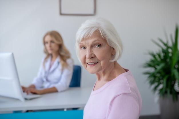 Paziente anziano seduto nell'ufficio del medico e che sembra contento