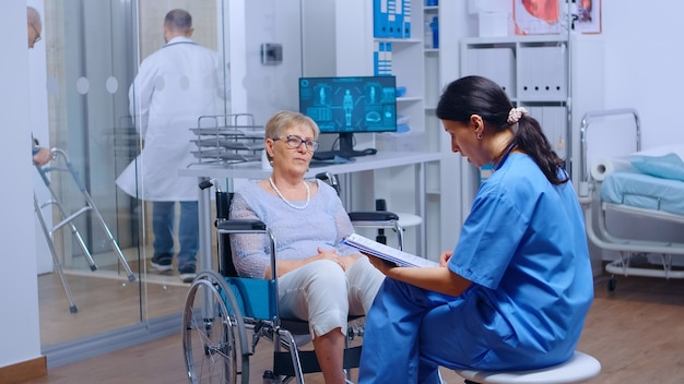 Paziente anziano con disabilità motorie su sedia a rotelle che chiede consiglio medico in una clinica di recupero o in ospedale. senior donna handicappata assistenza sanitaria supporto assicurazione medica persona paralizzata