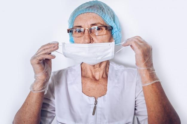 Il medico o l'infermiere maturo stanco triste stanco anziano della donna in un cappotto medico bianco, guanti, mette sopra la maschera di protezione che indossa l'attrezzatura protettiva personale isolata. concetto di sanità e medicina. pandemia di covid-19