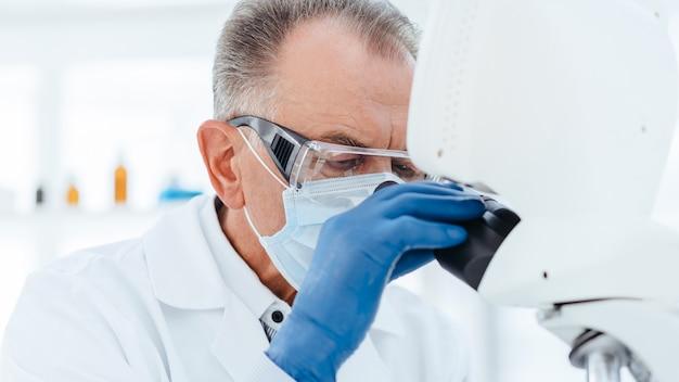 Scienziato anziano in una maschera protettiva guardando attraverso un microscopio