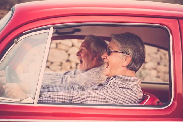 Coppia anziana anziana con cappello, con gli occhiali, con i capelli grigi e bianchi, con camicia casual, su un'auto rossa d'epoca in vacanza godendosi il tempo e la vita. con un cellulare allegro che sorride e impazzisce t