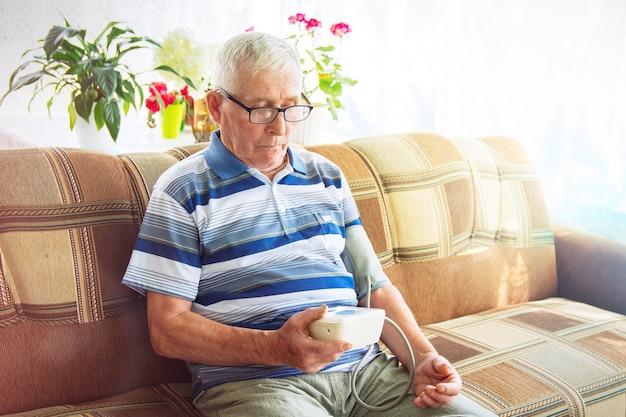 Un uomo anziano anziano con i capelli grigi e gli occhiali è seduto su un divano e si prende la pressione sanguigna con un misuratore automatico della pressione sanguigna. monitoraggio domiciliare, assistenza sanitaria