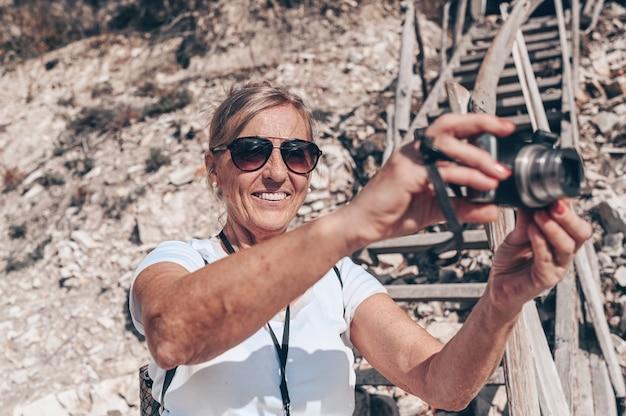 Anziani senior viaggio zaino in spalla donna matura turista a piedi scattare foto sulla costa
