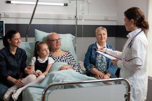 Paziente anziano malato anziano che riposa a letto con la famiglia premurosa accanto a lui