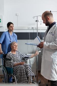 Paziente anziano malato seduto sulla sedia a rotelle dell'ospedale che riceve il trattamento attraverso la sacca per flebo e il ossimet...